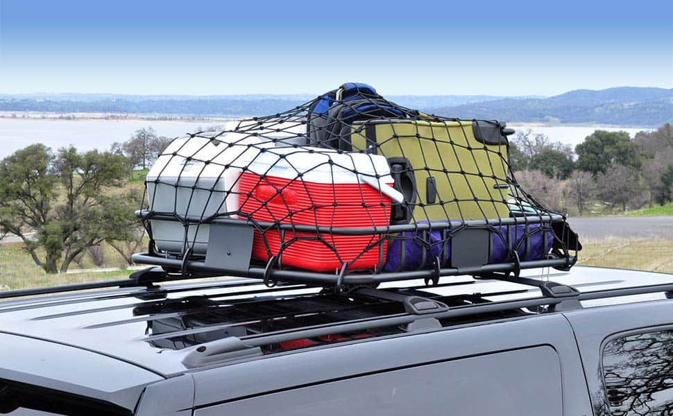 Cargo net storing gear on top of a car